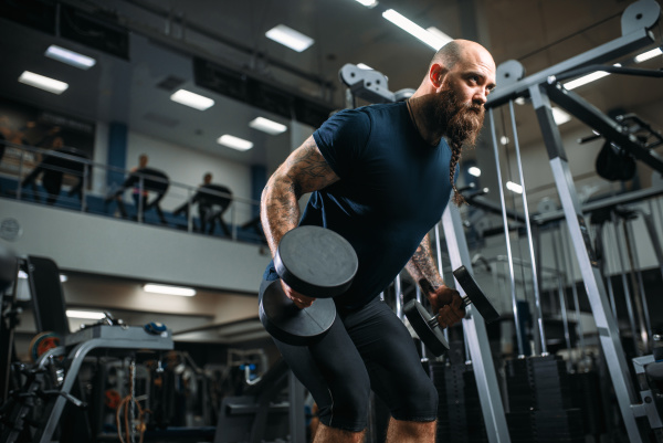 strong athlete with dumbbells training in