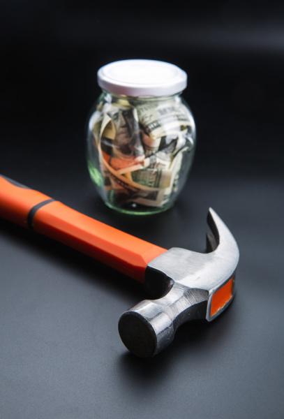 hammer against jar full of dollars