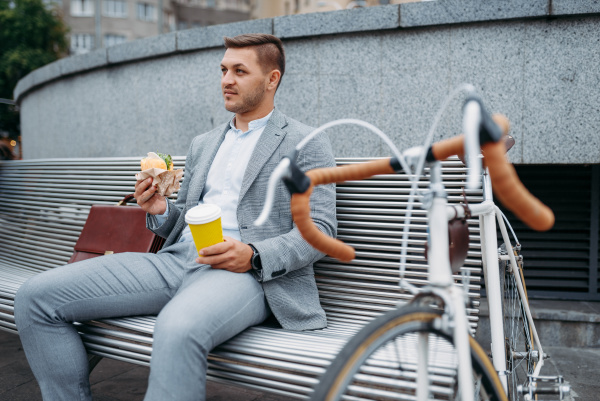 businessman with cycle eats lunch on
