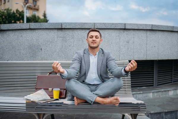 businessman resting in yoga pose on