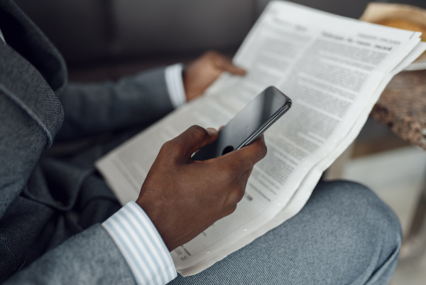 ebony businessman hands with newspaper and