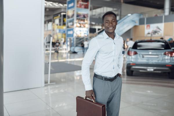 smiling businessman holds briefcase car showroom