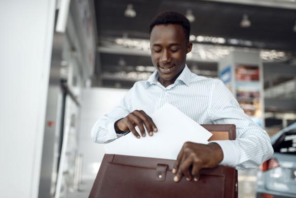 black businessman holds briefcase in car
