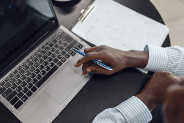 ebony businessman working on laptop top