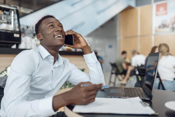 ebony businessman talking by phone in