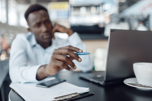 ebony businessman working on laptop in