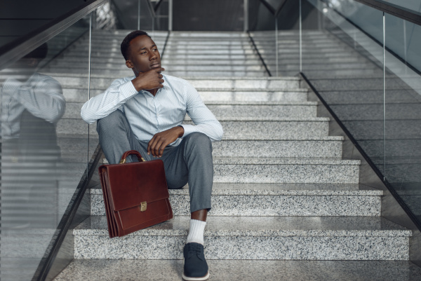 black businessman with briefcase sitting on