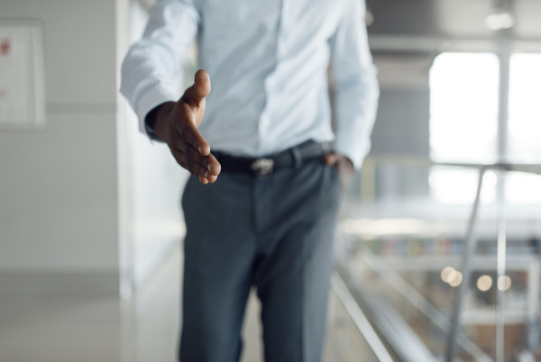 ebony businessman holds out his hand