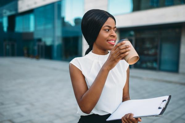 business girl grinks coffee from cardboard