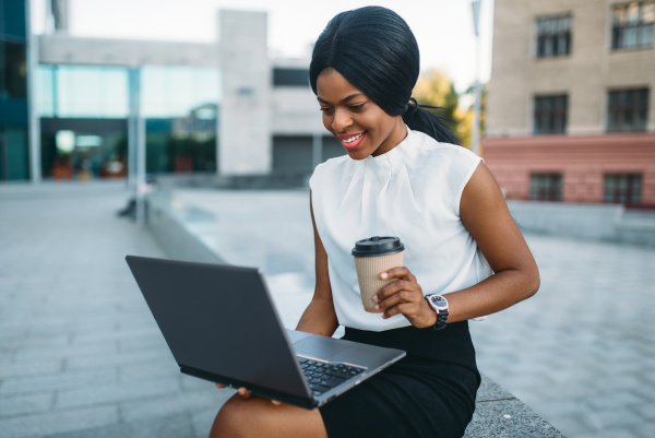 business woman uses laptop against office