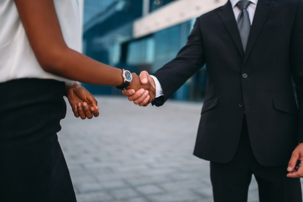 business woman and businessman shake hands