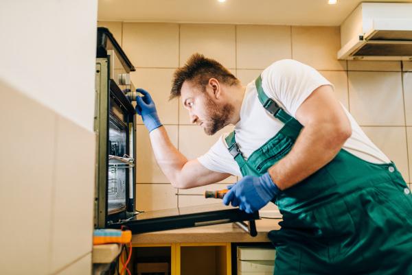 repairman in uniform checks the oven
