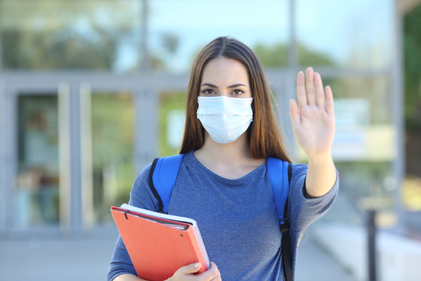 student with a mask gesturing stop