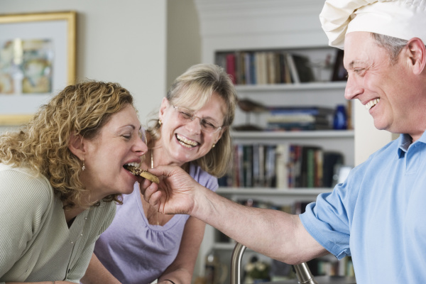 mature man feeding cookies to a