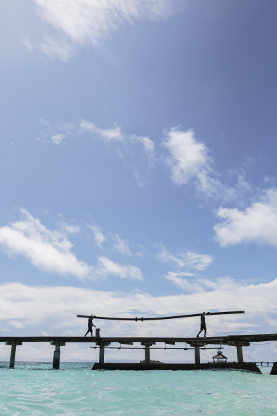 men on sunny dock over ocean