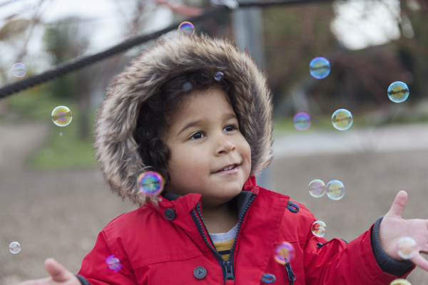 playful toddler boy playing with bubbles