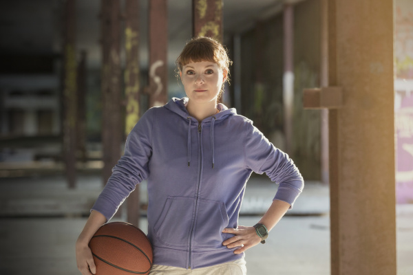 portrait confident young woman with basketball