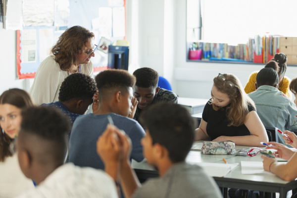 high school teacher helping students studying