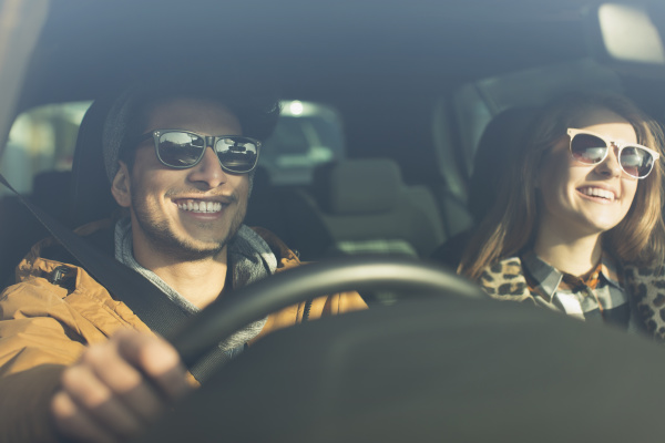 happy young couple wearing sunglasses in