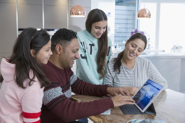 family using digital tablet at kitchen