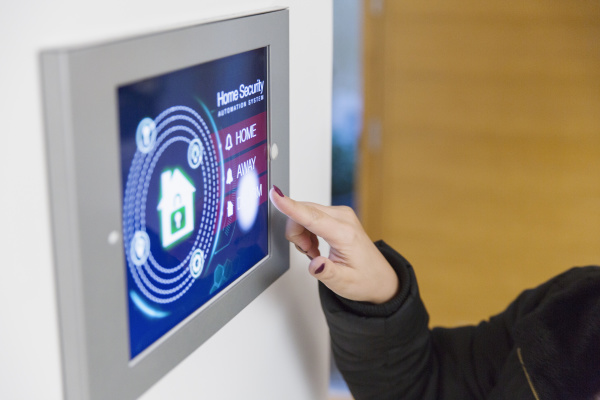 woman setting smart home security alarm