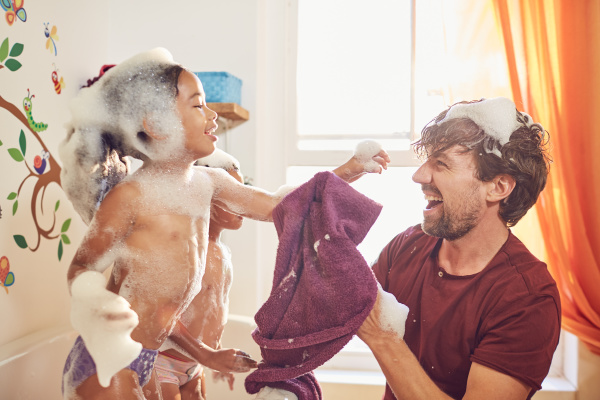 playful father giving daughters bubble bath