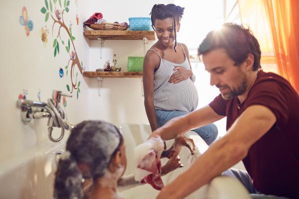 pregnant parents giving daughter bath