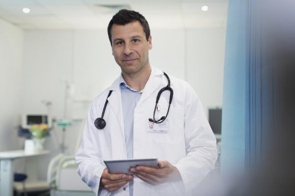 portrait confident male doctor using digital
