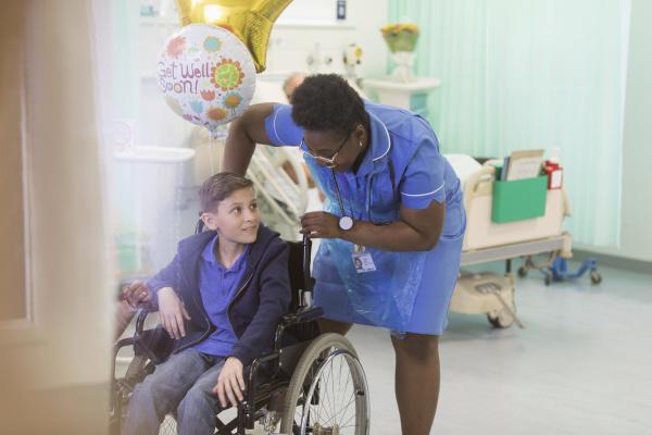 female nurse pushing boy patient in
