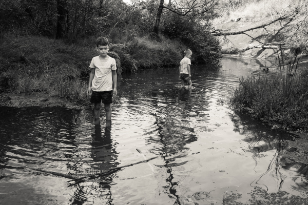 boys wading in river