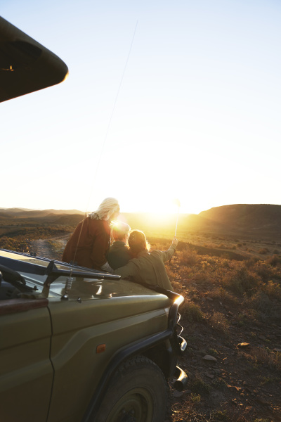friends on safari enjoying scenic sunrise