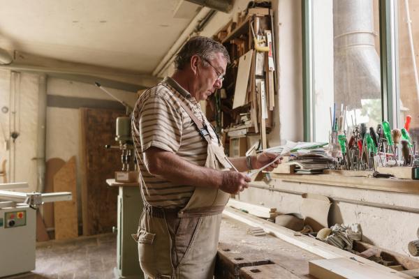 master carpenter at his workbench reading