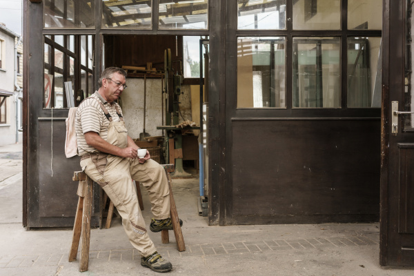 craftsman having cup of sitting on