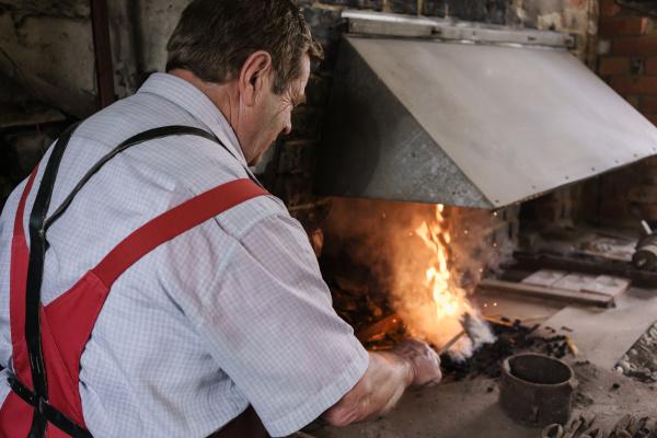 blacksmith in workshop heating metal in