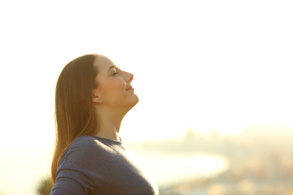 single woman breathing deeply fresh air