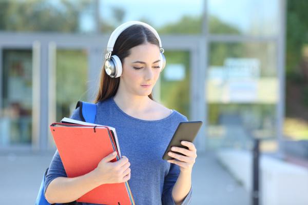 student girl wearing headset playing music