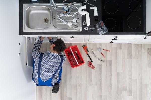 plumber examining kitchen pipes