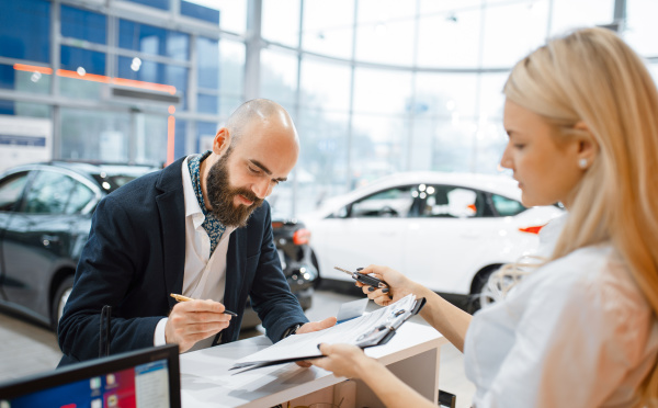 man signs a contract in car