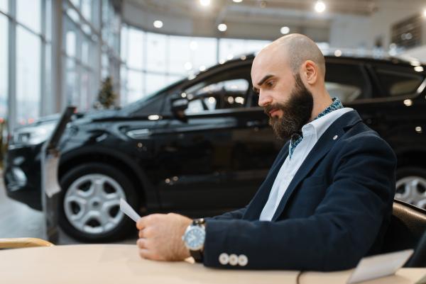man looks price on new automobile