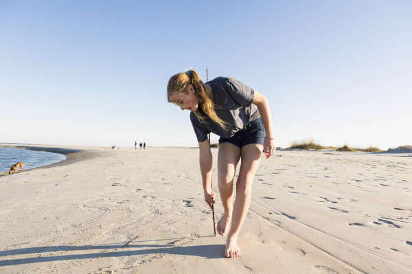 a teenage girl playing in sand