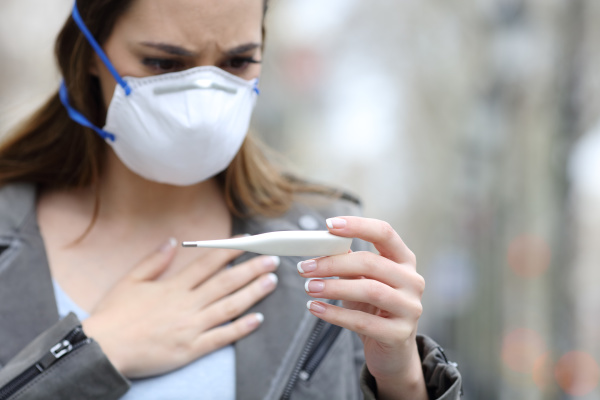 woman with protective mask checking thermometer