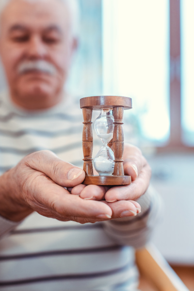 senior man holding hourglass in retirement