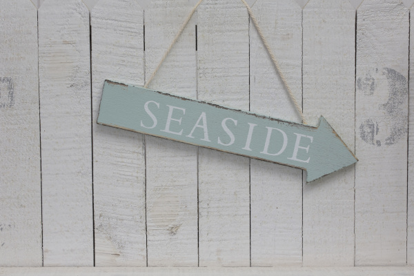 hanging seaside sign across white wood