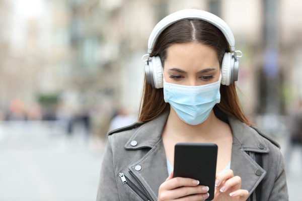 girl with mask and headphones reads