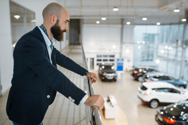 happy businessman poses in car dealership