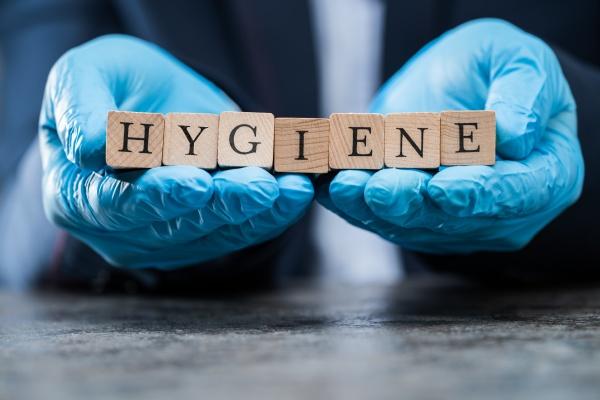 hand in gloves holding hygiene word