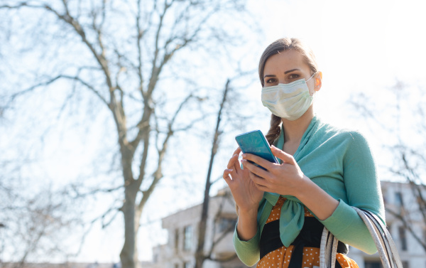 woman using her phone wearing mask