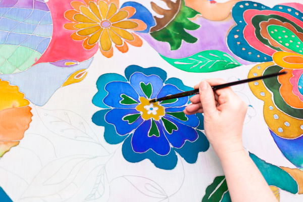 craftsman paints flower in batik on