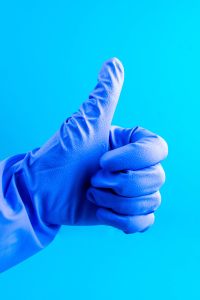 hand in blue medical glove shows