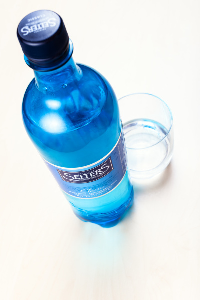 plastic bottle of selters and glass